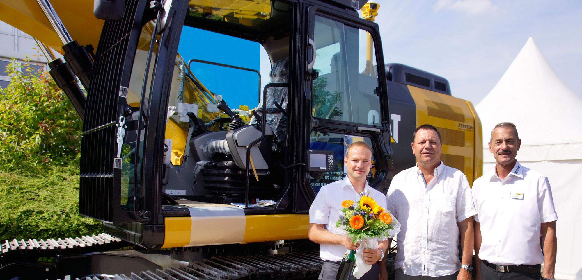 Blumen gab es nicht nur zum Jubiläum, sondern diese erhielt Detlef Lewerenz (Mitte), Inhaber der Umwelt-und Recycling-Bau GmbH, von Matthias Lützner (rechts), Niederlassungsleiter, und Matthias Lietsch (links), Verkaufsrepräsentant, bei der Übergabe eines neuen Kettenbaggers.
